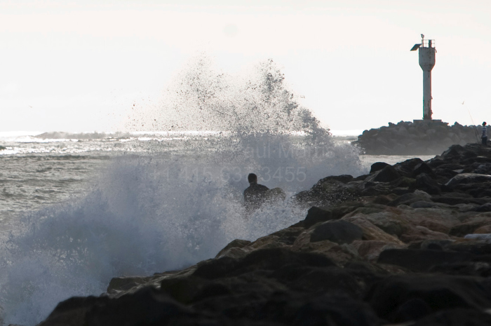 A man gets sprayed as the waves crash into the jetty at Pillar Point during a tsunami warning that was a result of an 8.8 earthquake in Chile February 27, 2010 in Half Moon Bay, Calif.